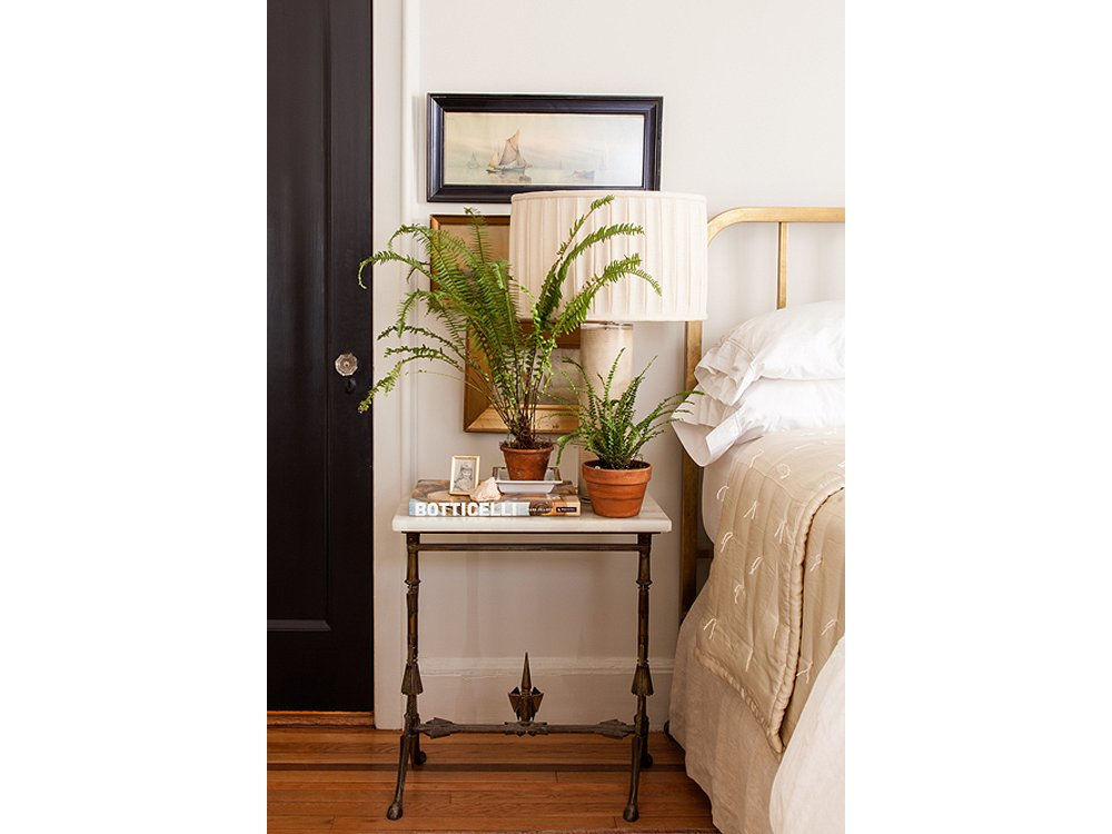 Plants on books in front of lamps in front of wall art makes for a rich mix on this bedside table.
