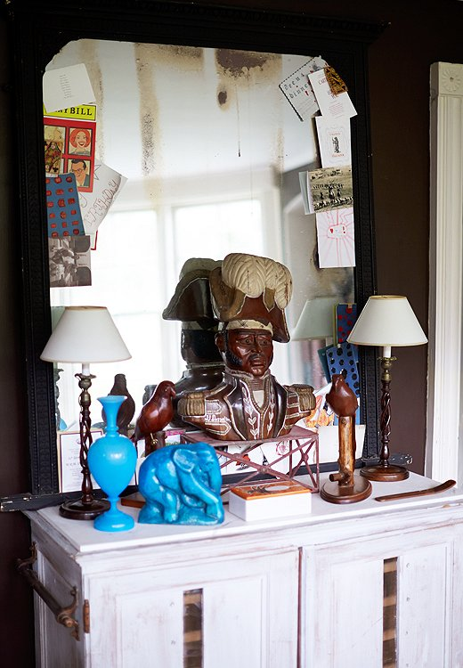 "Recent postcards and invites frame the mirror-turned-bulletin board in the study. The pairing of a 1930s elephant from France and the bust of a ""rather stern"" Haitian general demonstrates the duo's love of mixing time periods and design styles."
