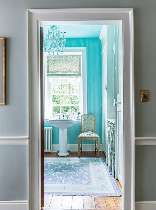 In the bathroom, theVenetian glass chandelier in a bright turquoise-aqua color was inspired by the original 1920s bathtub, which had been aqua.