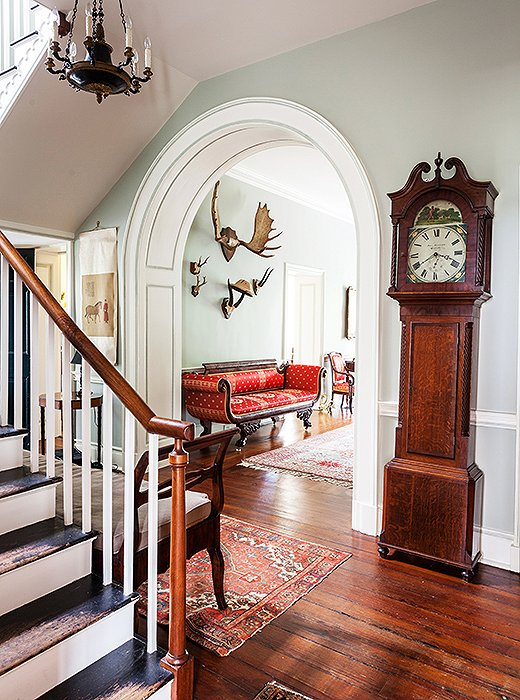 A rounded arch sets off a view past an inherited grandfather clock to moose antlers hanging in the entrance hall.