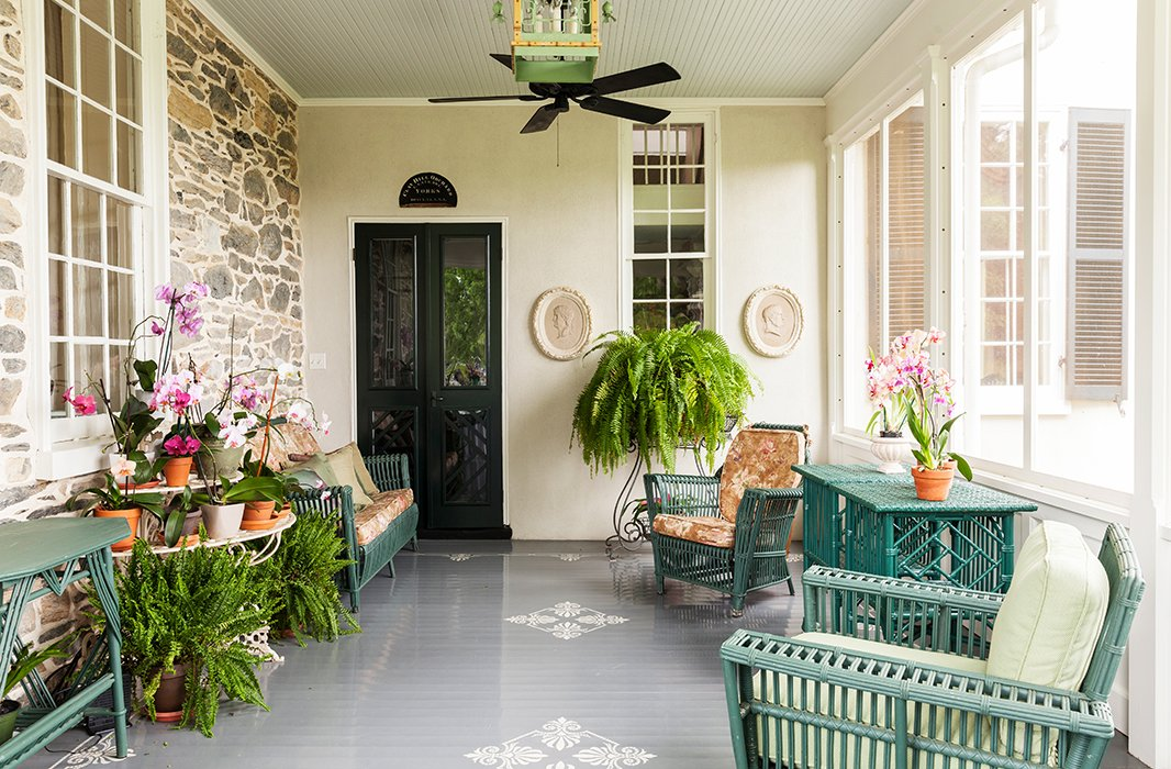 """The porch is furnished with antique wicker furniture, collected from various places. Elizabeth painted itall Charleston Green, a deep green with a """"giant dollop of black in it."""""""