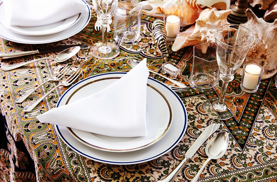 Antique glassware sparkles atop an Indian bedspread-turned-tablecloth.