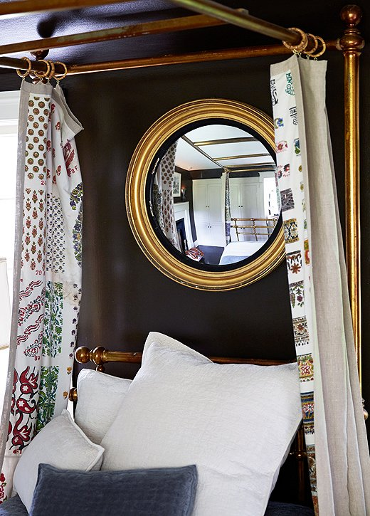 "When open the curtains frame a 19th-century gold bull's-eye mirror; when closed they show their pattern only to the resident of the bed. ""I love the element of surprise,"" Ross says."
