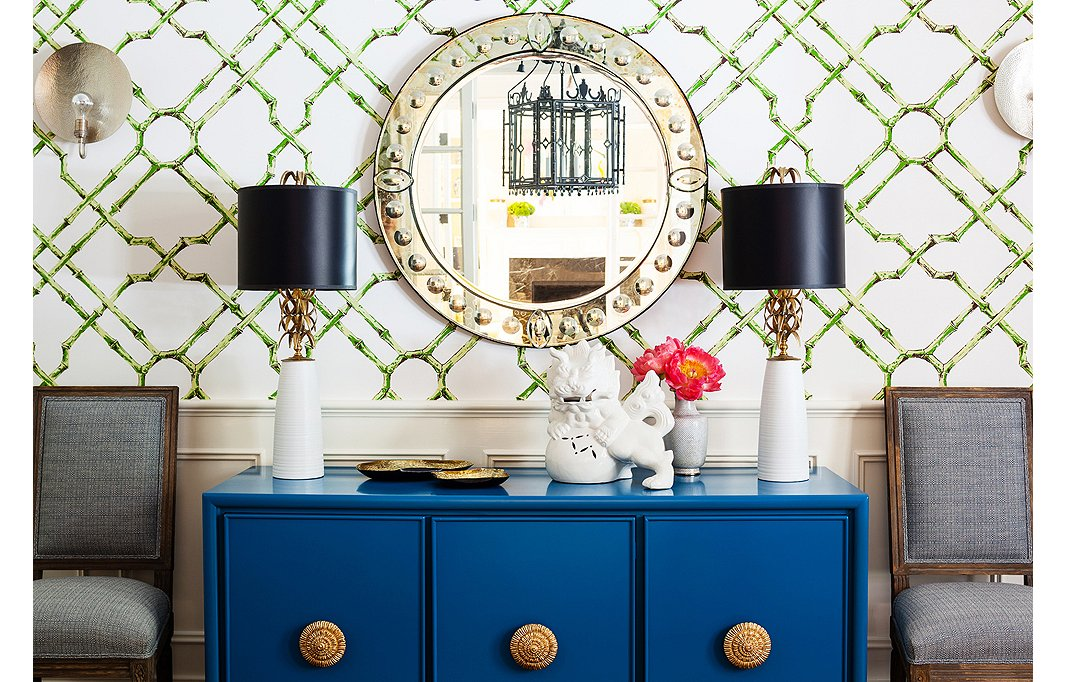 An antiqued Venetian glass mirror makes a subtle statement when paired with patterned wallpaper and a poppy console. Photo by Nicole LaMotte.