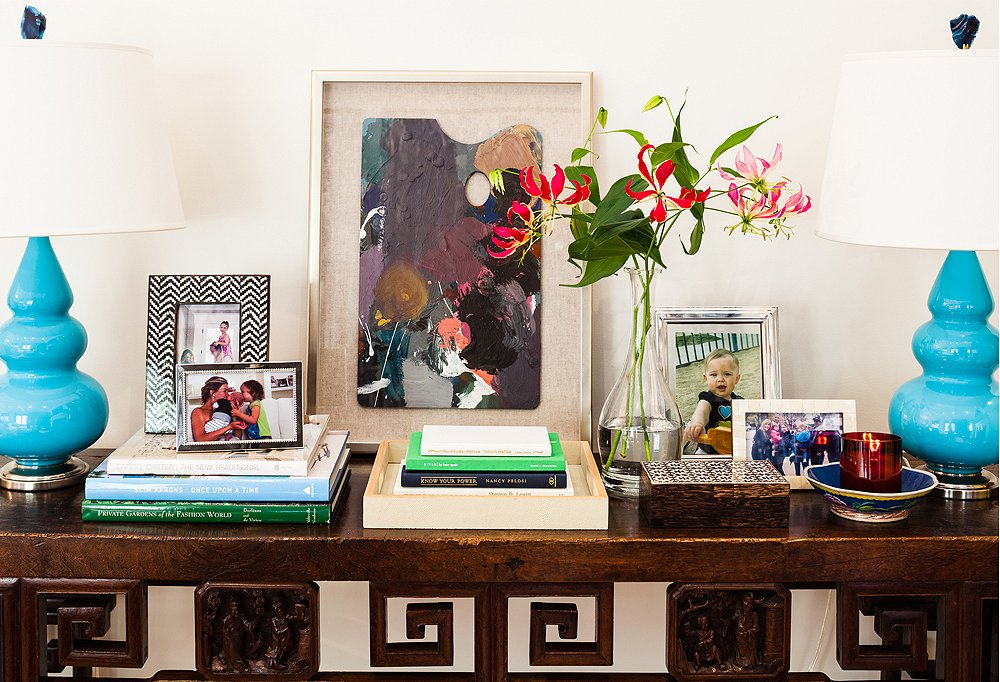 "A console in the living room holds family photos in a mix of frame styles. ""I wanted people to walk in and get that this is a young family home,"" says Lauren. A pair of boldly hued lamps draw attention to the display."