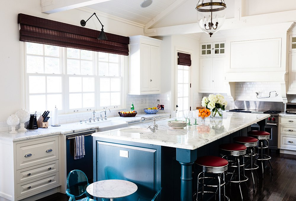 In this kitchen designed by Hillary Thomas, a row of comfy counter stools tuck away to allow for more walking space.