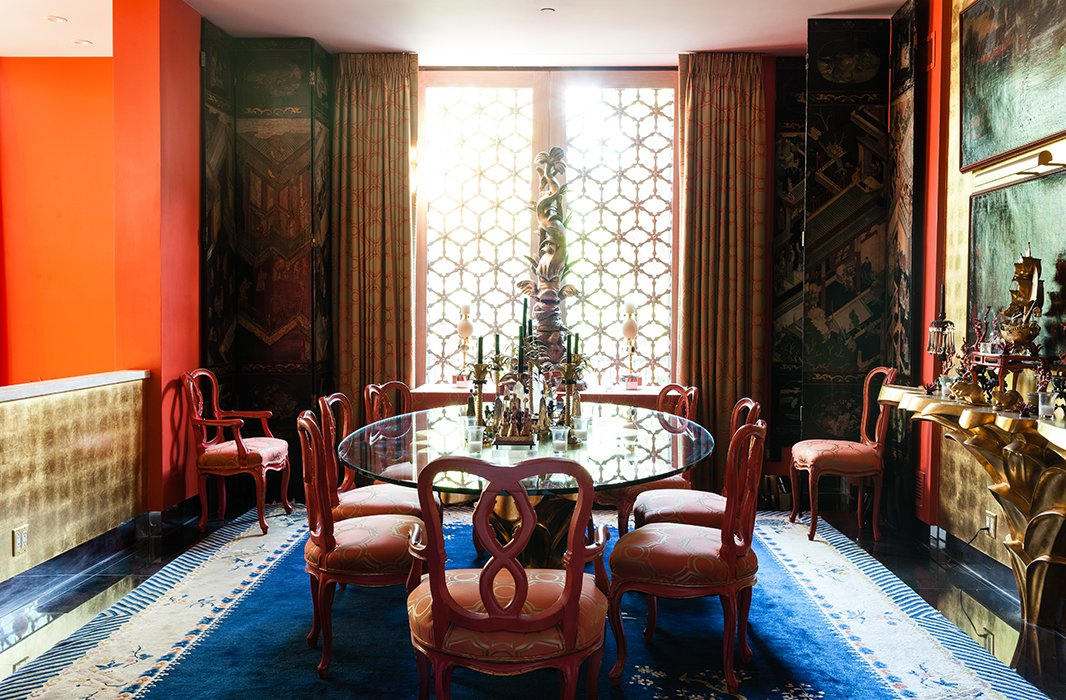 The 11-foot-high dining room features 18th-century Venetian chairs and an antique Chinese rug. Hutton split up a 12-panel coromandel screen from JF Chen and placed three panels in each corner of the room.