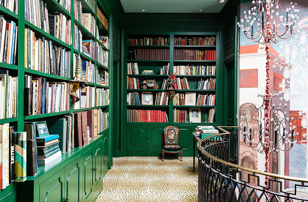 Lacquered in emerald green, the built-in wall-to-wall bookcases are home to eclectic objects, such as scale models and seashells, as well as a colorful array of favorite books.