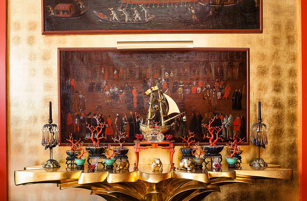 Seventeenth-century Venetian paintings hang above a console created by costume designer Don Loper in the 1940s. The 18th-century Chinese lacquer coral branches are from the collection of Elsie de Wolfe.
