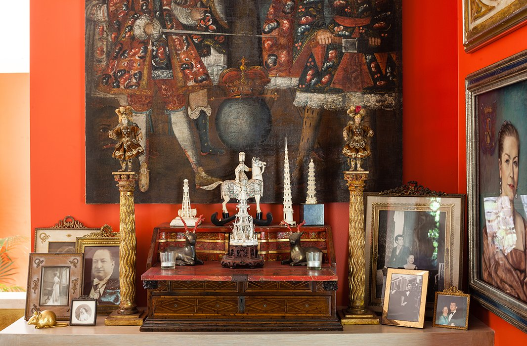 Family photographs include, on the left, one of Hutton's grandfather, who was president of Bolivia from 1934 to 1936, and another of his grandmother on her honeymoon. The Spanish Colonial archangels on gilded columns are from an antiques show.