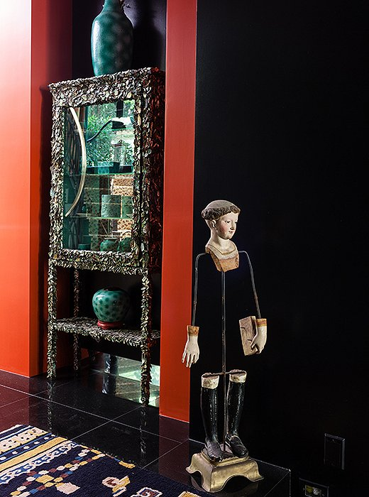 In a passage near the entry, an 18th-century statue of an Italian saint stands guard by an abalone shell, a coral branch, and a pearl display case made by Duquette.