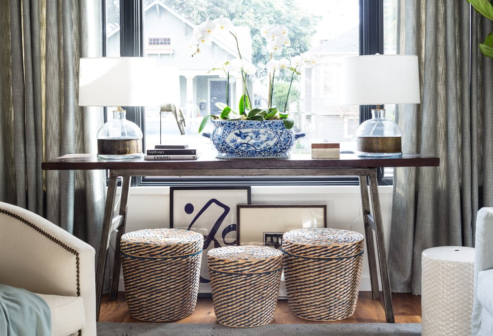 """Alex's motto is """"leave no space undecorated,"""" so he tucked art and lidded baskets (a mom's best friend) under the console to avoid a blank white space."""