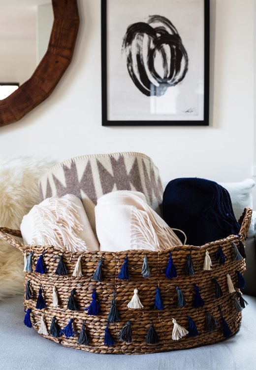 Rather than letting blankets languish in your linen closet (where they'll never see the light of day) ortucking one around your couch(which might be too bold a statement), roll them up in a pretty basket so that they add a touch of color and are easily accessible on movie night.
