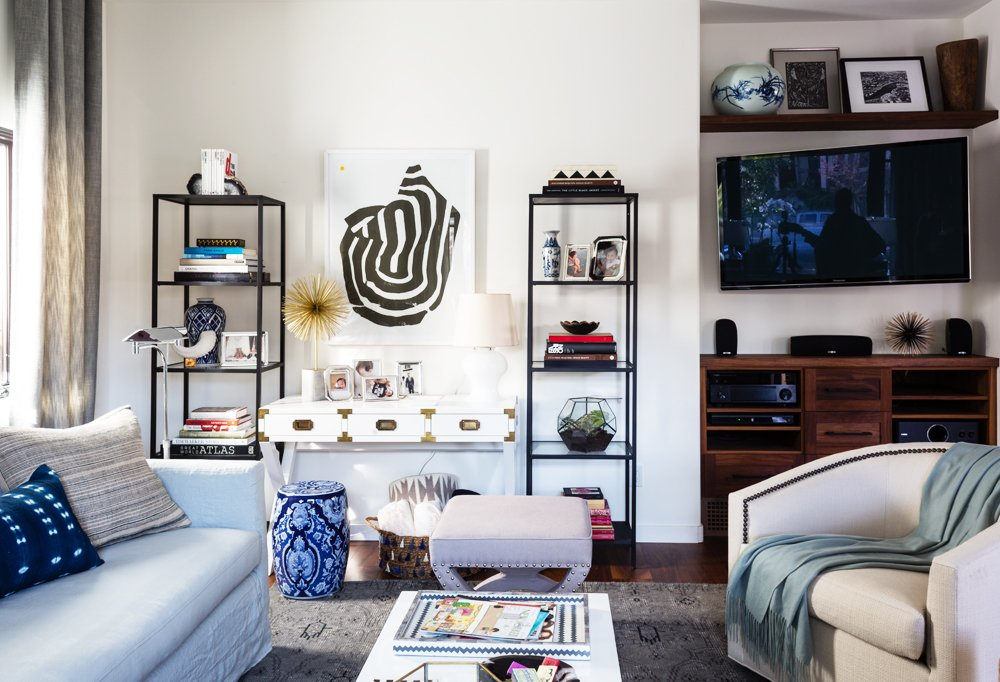 Alex based the height of the pieces in the room off Erica's lofted TV set. He brought the drapes up and opted for tall bookshelves to balance themout, while hanging the artwork between a little lower to play with theeye.