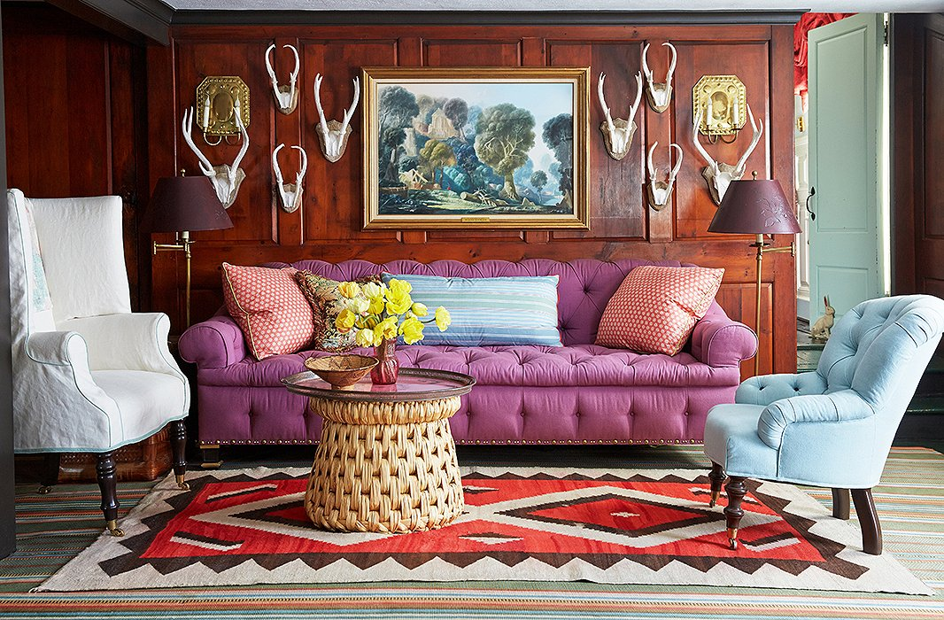 A theme running throughout the house, antlers stand out in stark relief from pine paneling. Jeffrey's own designs (the sofa and the armchairs), a 19th-century French tole tray on a raffia table, and Native American carpets round out the eclectic mix.