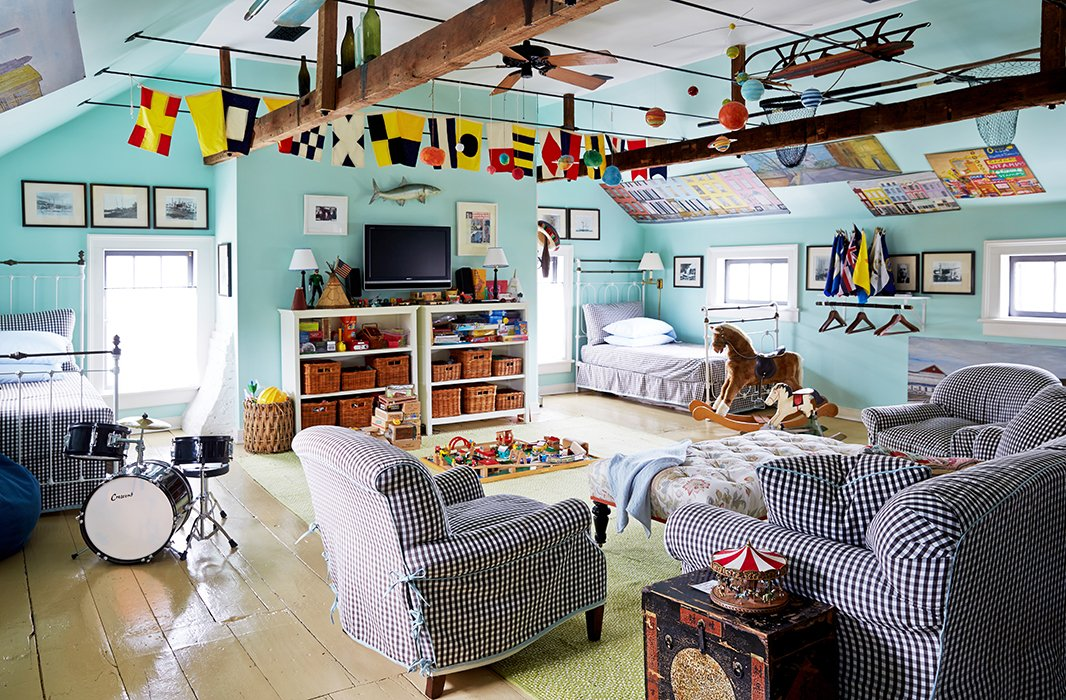 Transformed into a fantasyland playroom for Christoph and his pals, the attic room is strung with vintage signal flags that almost appear to be flapping in the sky. Twin beds and cushy upholstered pieces are sharply outfitted in a black-and-white gingham from Malabar.