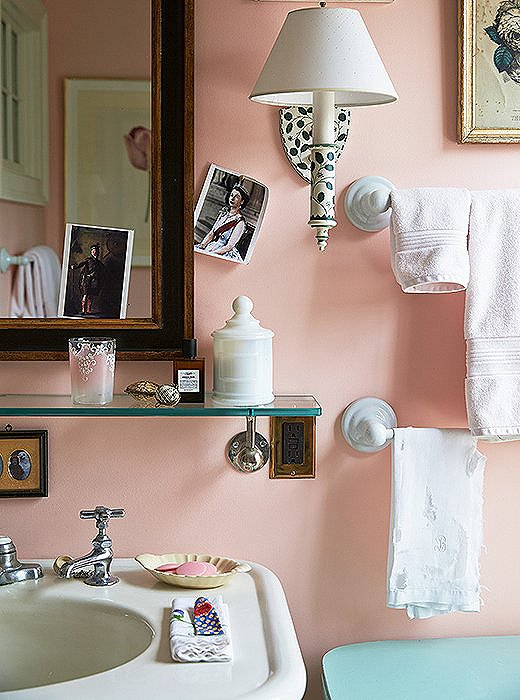 Wanting the ladies' guest bath to feel romantic and pretty, Jeffrey painted it peach sorbet. The walls pull double-duty as a gallery for an ever-changing rotation of pictures and postcards.
