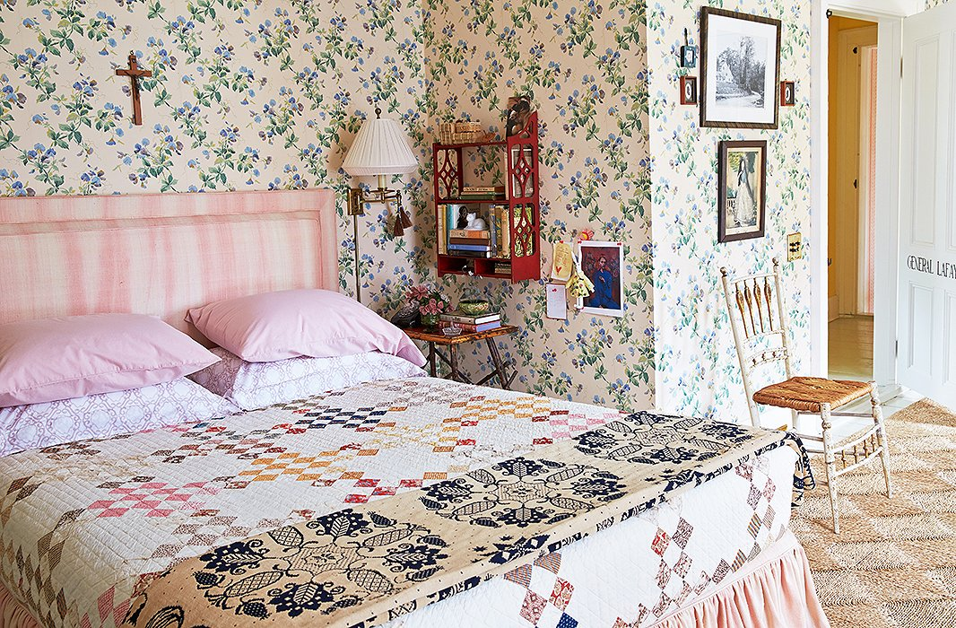 Inside General Lafayette's bedroom (aka the ladies' guest bedroom), sweetly trellised sweet peas crawl up the wallpaper behind a bed made with pink-and-white Sferra linens tucked cleanly under an antique quilt.