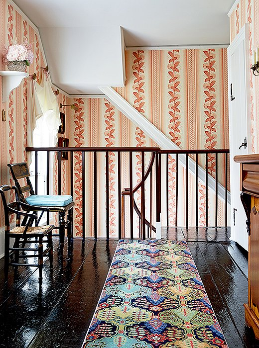 Follow the hydrangea wallpaper upstairs and you'll find a wool Persian-style runner protecting black-painted pine floors.