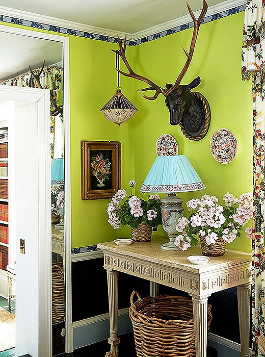 The lime-green walls play up the whimsy in this nook's juxtaposition of unlikely objects (including the lantern hanging from an antler). Photo by Tony Vu.