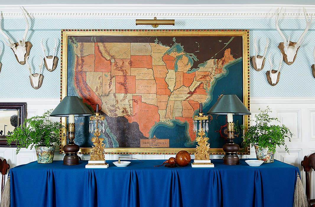 In the entrance hall, antlers collected over the years and a pair of 19th-century gilded metal oil lamps converted to electricity flank a vintage map.