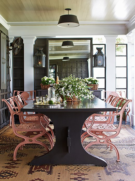 Step out onto the porch, and you'll find a dream dining scene composed geranium-pink cast-iron chairs tucked into a table designed by Jeffrey.