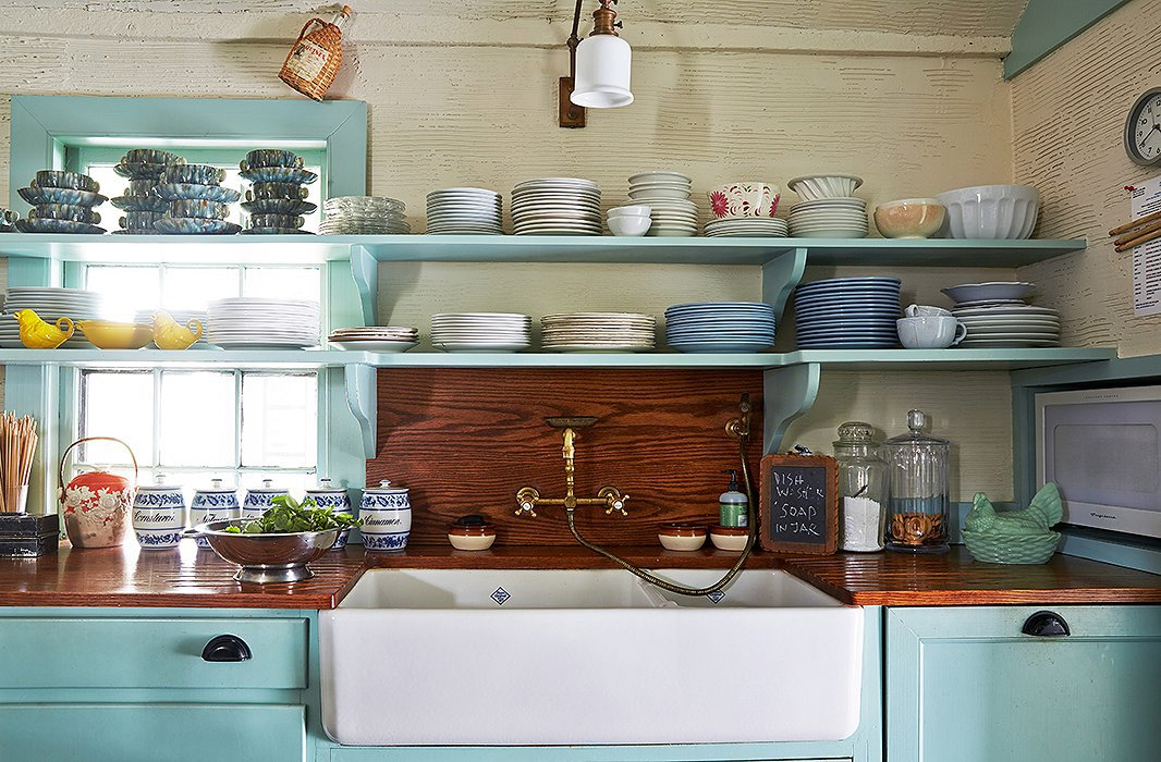 "Above the Shaws farm sink and antique brass fixtures sits a portion of Jeffrey's immense tabletop collection, both complete and partial sets of mostly ironstone china. ""I have a vast trove for entertaining, which is always being added to,"" he says."