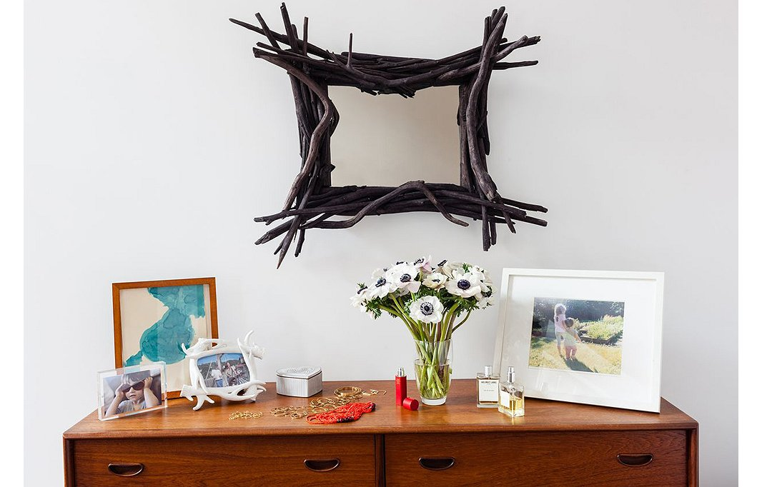 The top of a midcentury dresser in the bedroom serves as a catchall for jewelry, perfume, and treasured family photos. Above it, a branch-framed mirror lends a touch of natural beauty.
