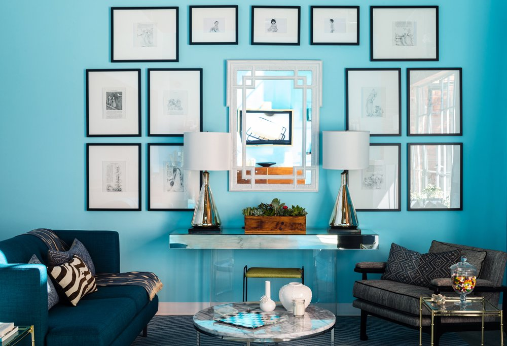 The space sticks to a limited color palette of blue, black, and white, with eye-catching mirrored surfaces, like the pair of 1960s lamps and the vintage console, and hits of wood for a bit of tonal warmth.