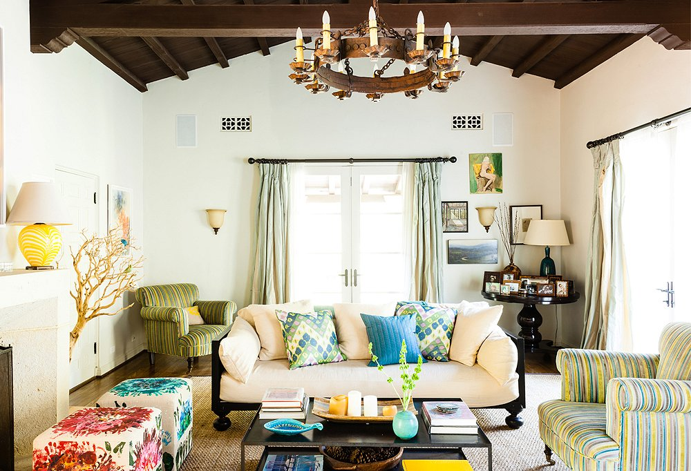 Elegant, contemporary furnishings balance out the living room's hacienda-style wood ceiling and rustic iron chandelier.