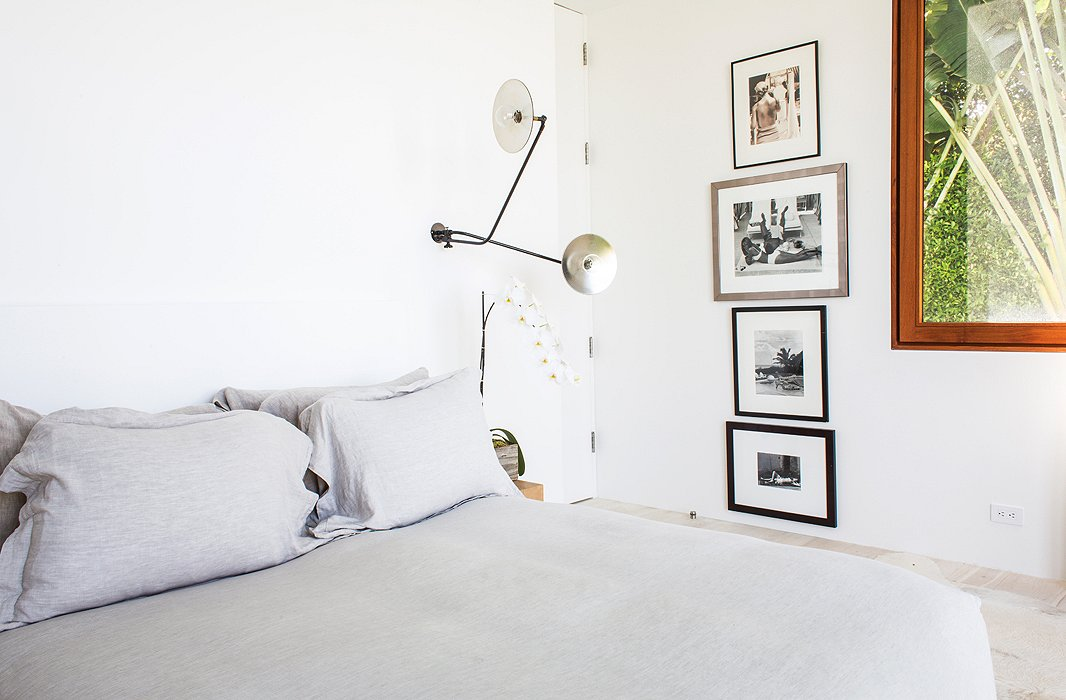 "The minimalist sconces are from Workstead. ""I prefer sconces to lamps because they disappear,"" says Kelly. ""They make less of a statement in the room, and they don't take up space on a side table where you already have your iPad and phone and computer."""