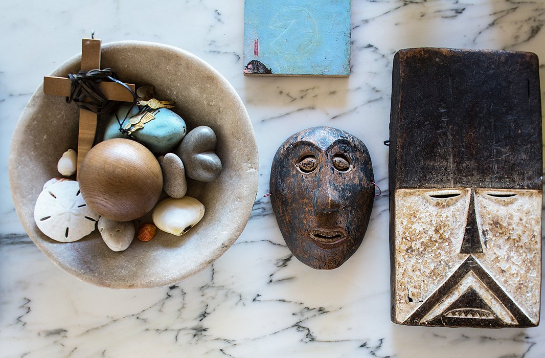 Though the house has little color, it abounds in natural textures. A rugged bowl of shells and rocks shares shelf space with two African masks.