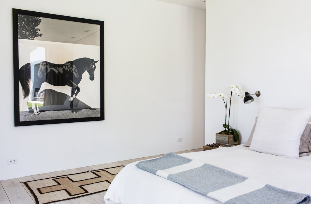 Bleached oak floors, pale walls, and matching linens make for a serene retreat. The horse photographs throughout the house, testament to Kelly's love of horses and years of competitive riding, are by Steven Klein.