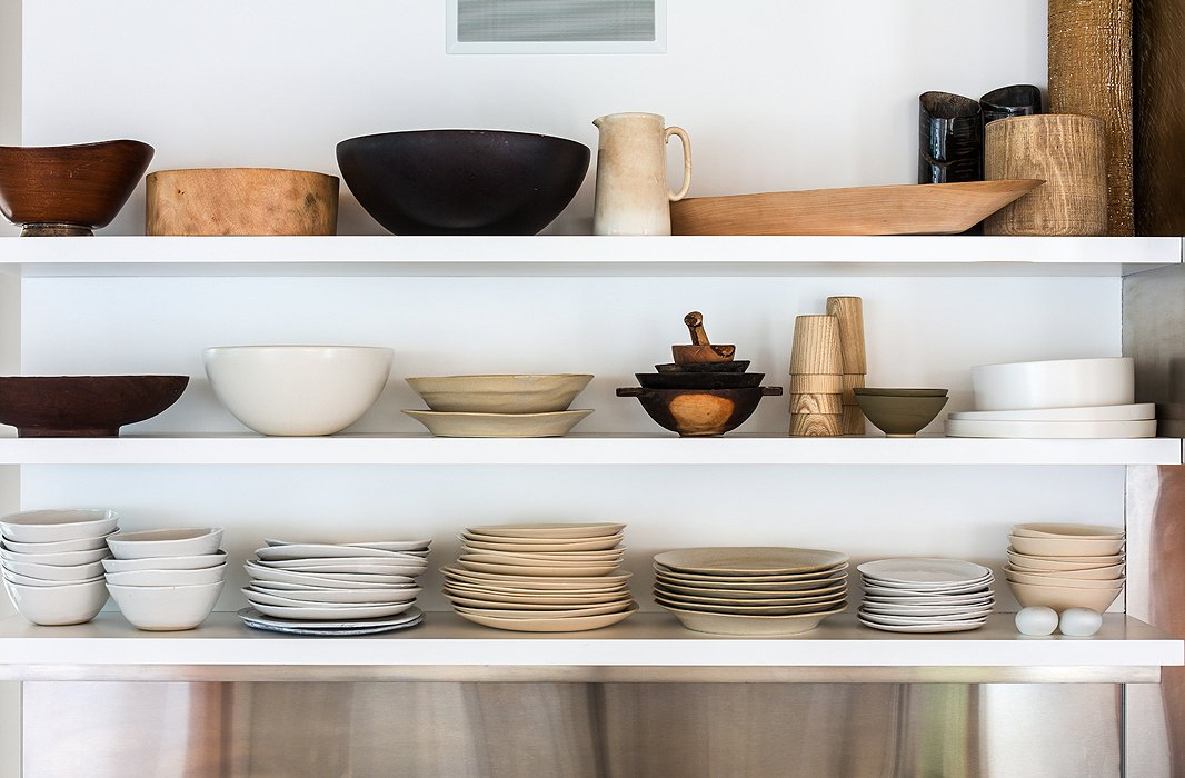 The house's airiness extends into the kitchen, where open shelving holds Kelly's collection of dishes and serveware, all in the same low-key palette and natural materials as the rest of the home.