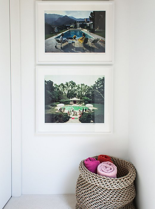 Color photographs by Slim Aarons and a basket of towels—set out to make them easy for guests to grab before hitting the pool—provide striking pops of color in an otherwise subdued home.