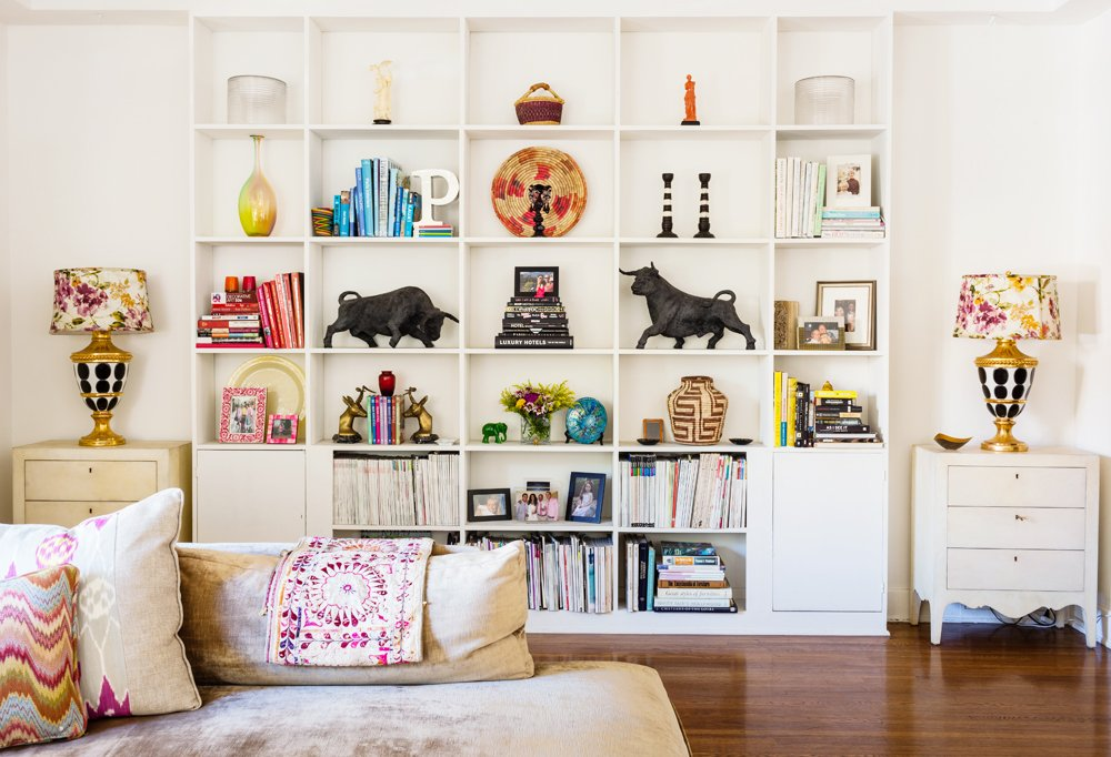 The bookshelves were arranged to highlight Kim's favorite pieces—like the midcentury plaster bulls (she's a Taurus)—and feel airy and orderly. Her tips: Color-coordinate to achieve calm, group smaller pieces when possible, and think both vertically and horizontally.