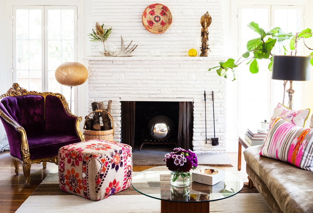 "Beside the fireplace was one of two purple upholstered chairs that Kim scored at a Paris flea market and has had for more than 15 years. ""They've worked in every home I've ever had,"" she says. ""They're the perfect example of 'buy what you love.'"""