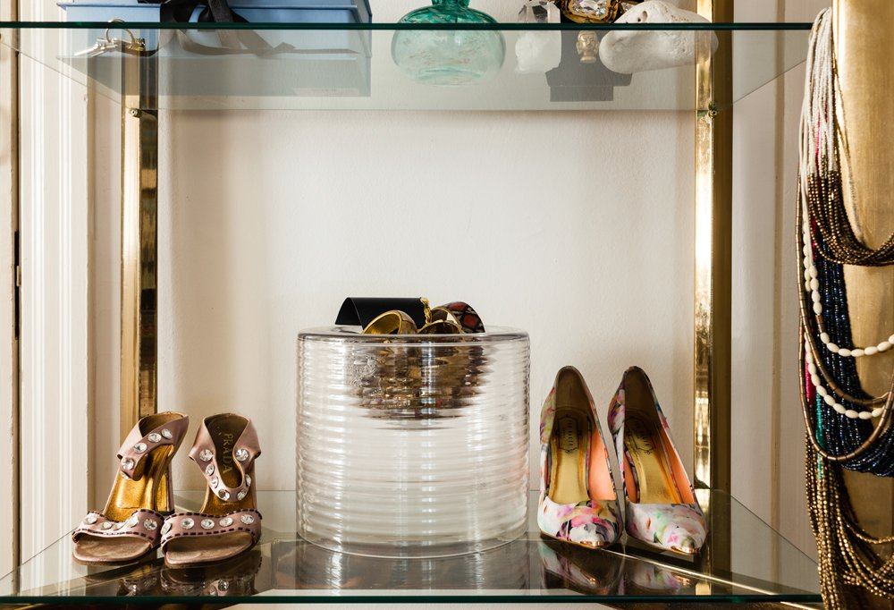 In the brass-and-glass bookcase in her bedroom, Kim mixed things up by displaying her shoes, letting her current favorites share shelf space with personal photos and frequently worn jewelry.