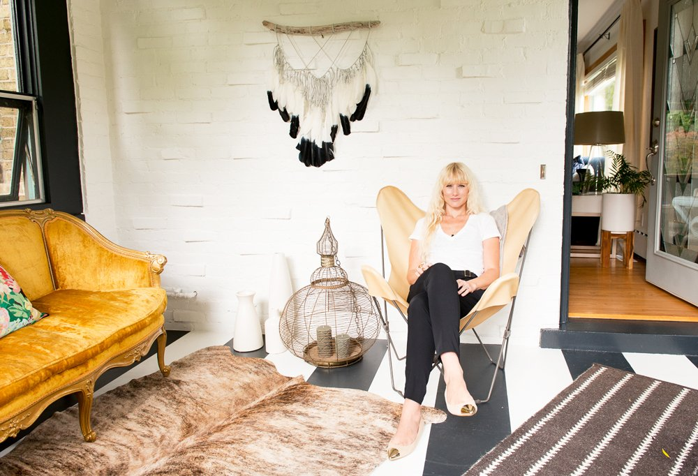 After a long day's work, Kristen kicks back in her entryway, which sports a striped floor she painted herself and a mix of vintage finds that exemplify her eclectic, effortlessly cool style.