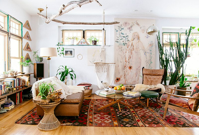 Adding to the airy feel of the space, the white walls in this light-filled living room are the perfect backdrop for the vibrant kilims, tribal patterns, and plants.