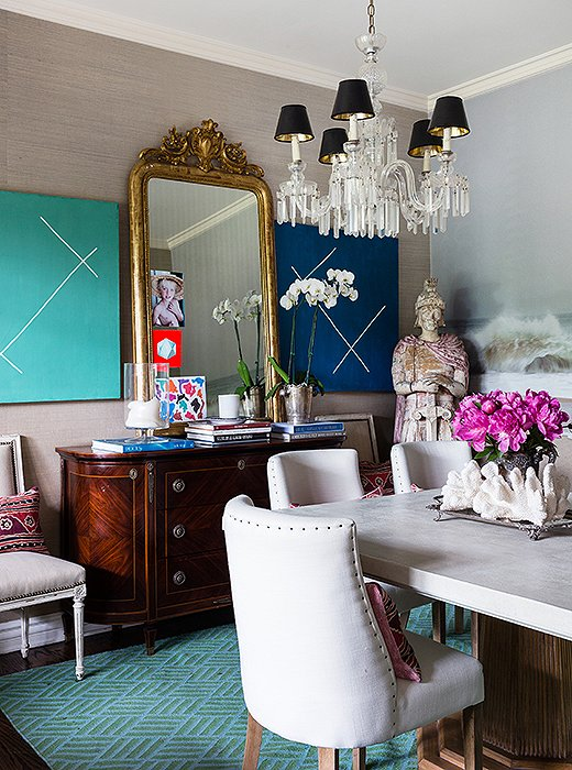 The paintings in the dining room are by Andrew Gellatly, the mirror is an Italian family heirloom, and the sideboard comes from One Kings Lane.