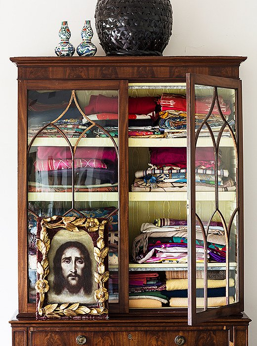 "This inherited glass-front armoire has followed Lulu from home to home. ""It holds everything extra in my life—mostly antique textiles from my travels through Turkey, Peru, India, and South Africa."""
