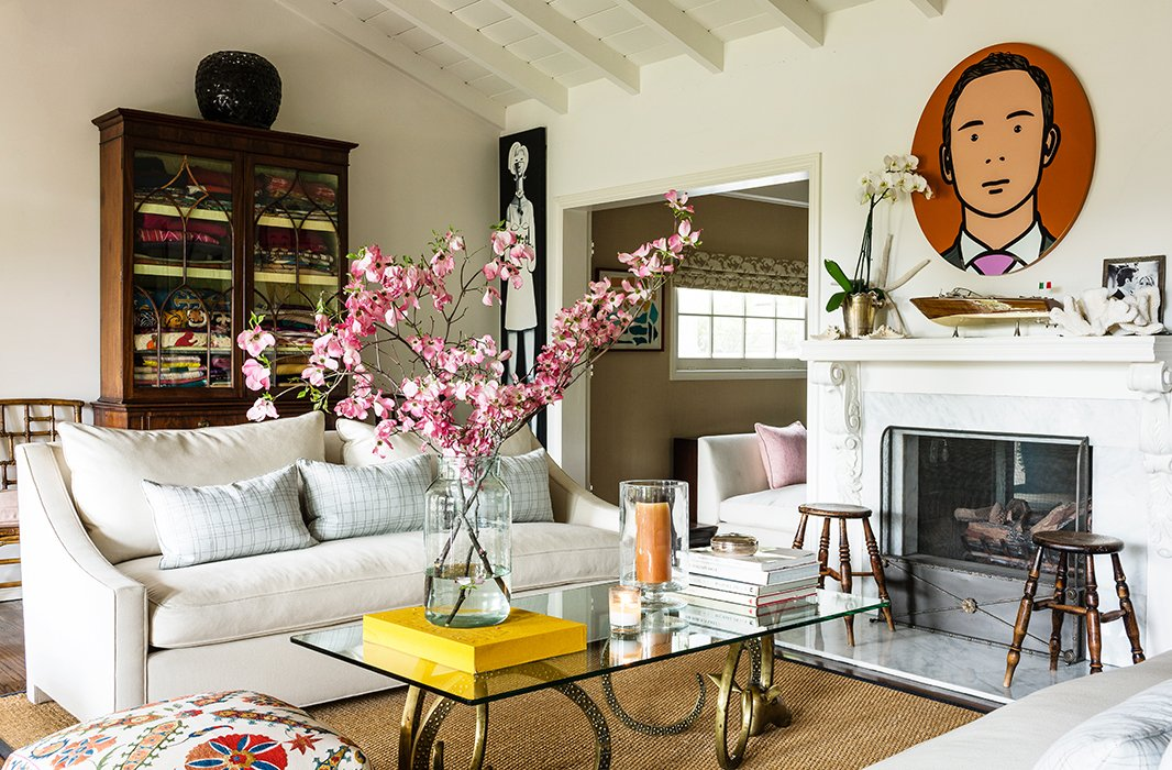 The sitting room is an airer take on New England style. Lulu topped a pair of stylized ram's heads with glass to make the coffee table, while a piece by British artist Julian Opie hangs over the mantel.