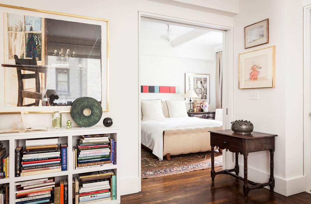 A pale bed and walls let artwork shine. Hanging over the bed (the Calla, designed by Mariette for Hickory Chair) is a set of paintings by Yuko Shiraishi; outside the door hangs a watercolor by Carolyn Brady.