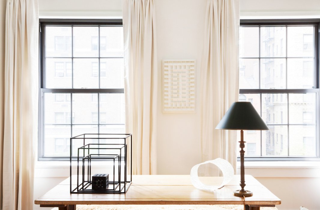 The pale backdrop of an English Regency refectory table highlights the striking silhouettes of an antique lamp and two very contemporary works of art: a set of metal cube frames and a glass sculpture. The paper wall art is by Dutch artist Jan Schoonhoven.