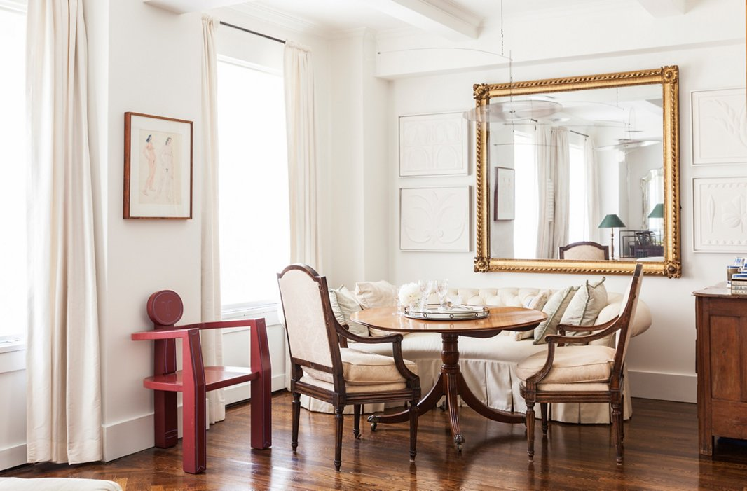 An oversized, rectangular mirror is flanked by artwork in the dining area of designer Mariette Himes Gomez's home.