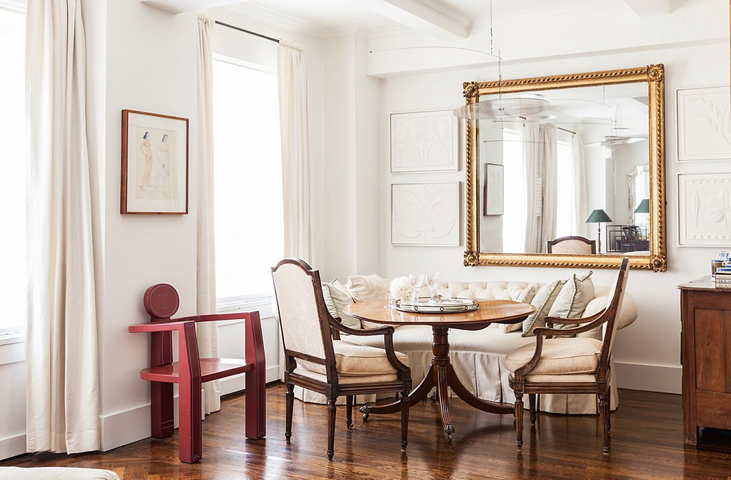 An oversize rectangular mirror is flanked by artwork in the dining area of designer Mariette Himes Gomez's home.