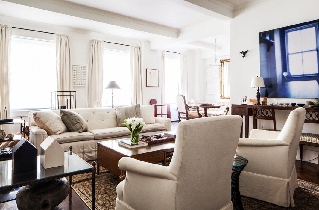 """""""There are no children, so I don't have to be careful,"""" Mariette says of her white upholstery. The sofa was designed by Syrie Maugham—a legendary designer of the 1920s famous for her all-white rooms—and the coffee table is by the American midcentury designer Paul McCobb."""