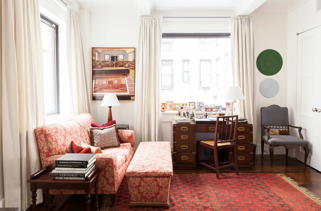 In her otherwise pale apartment, Mariette's home office, featuring an antique couch and ottoman covered in original fabric and a striking black-and-red rug, testifies to her love of color and pattern. It's also her favorite place to relax and watch the news. The painting is by George Deem and the oil-on-plywood discs are by Rupert Deese.