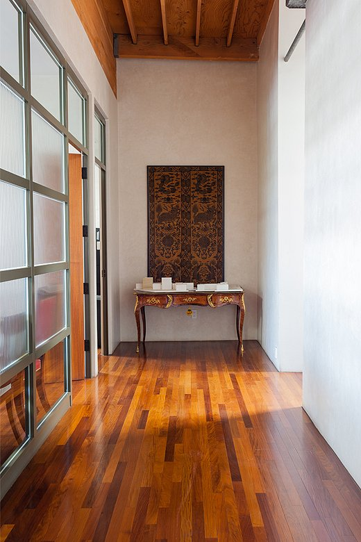 In the hallway leading to the main conference room, a 19th-century Chinese panel hangs above an antique desk.
